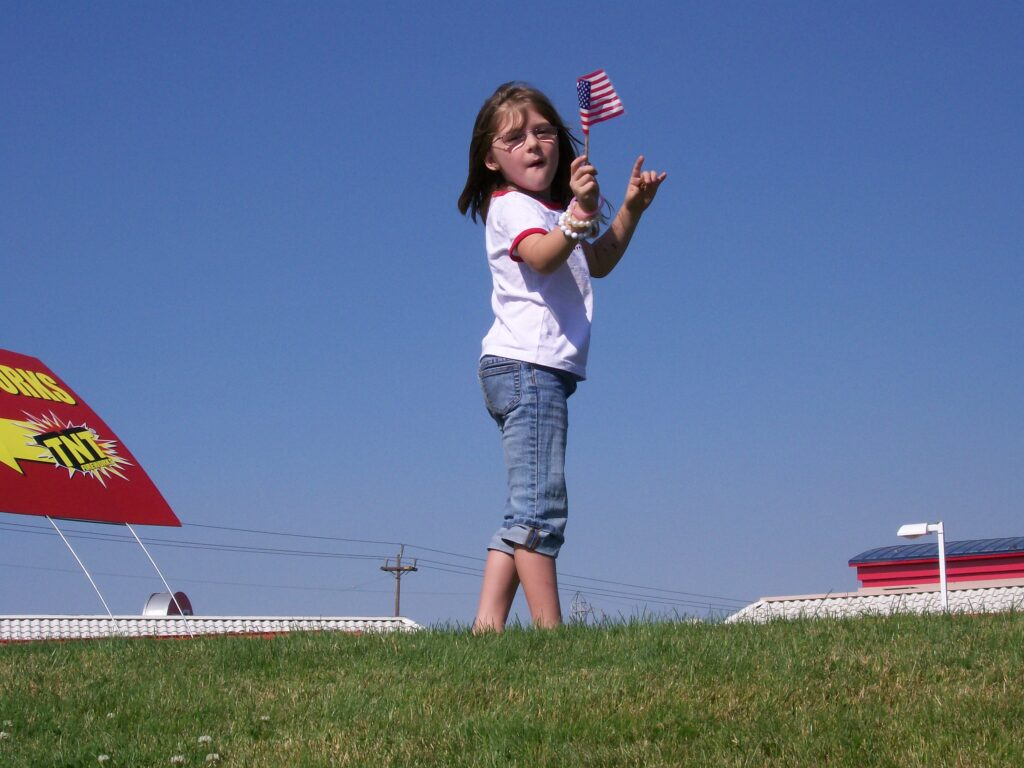 photo of Micayla waving at passersby (2008)