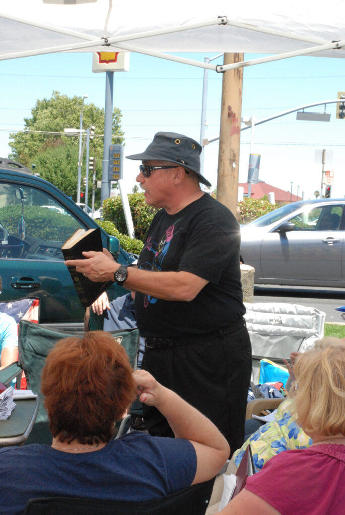 photo of Pastor leading Sunday worship at the booth (2012)